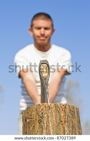 Close up of axe head splitting a log with a male figure with narrow depth of focus against a beautiful blue sky - stock photo