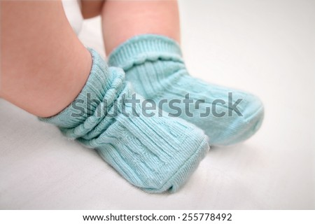 Close up of babies feet wearing blue cotton socks - stock photo