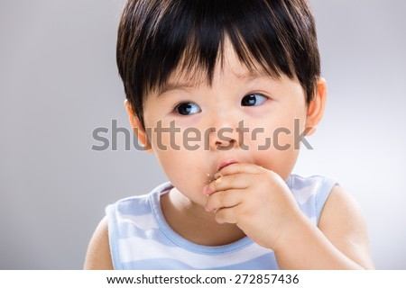 Close up of baby boy eating the finger food - stock photo