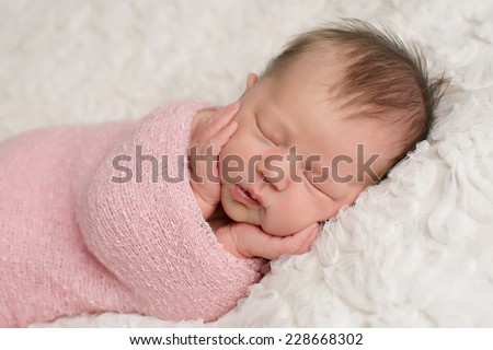 Close up of baby girl with her hands on her cheeks - stock photo