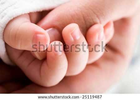 Close-up of baby?s hand holding mother?s thumb - stock photo