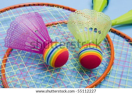 Close-up of badmington rackets with balls on a blue background - stock photo