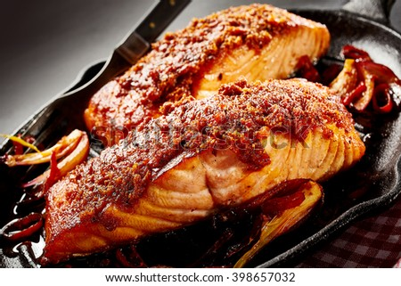 Close up of baked salmon dish for one serving next to fork in black cast iron pan