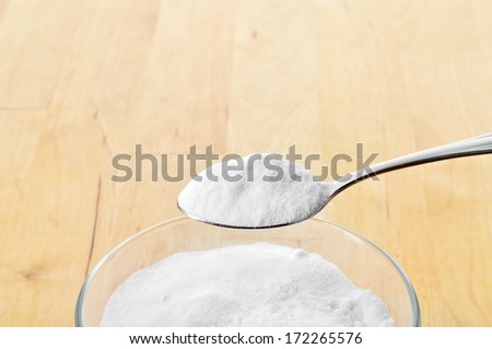 Close-up of baking soda on spoon against background of glass of water on wooden table. Bicarbonate of soda. - stock photo