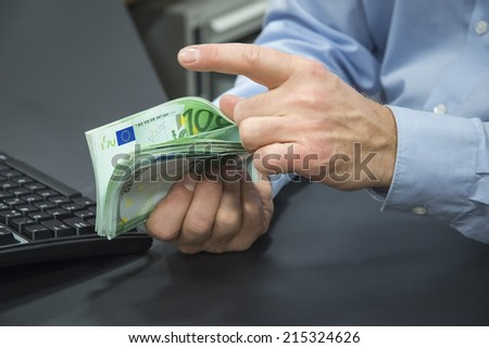 Close-up of bank clerk counting 100-euro bills - stock photo