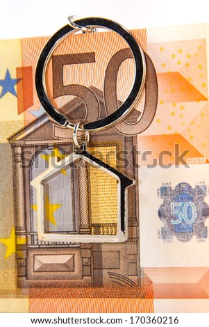 Close up of banknotes of fifty euro on white background with house-shaped key-chain, concept for houses on loans  - stock photo
