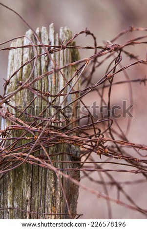 Close up of barbed wire on an old farm fence post - stock photo