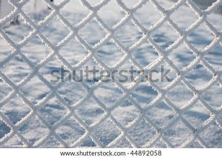 Close-up of barbwire covered by snow - stock photo