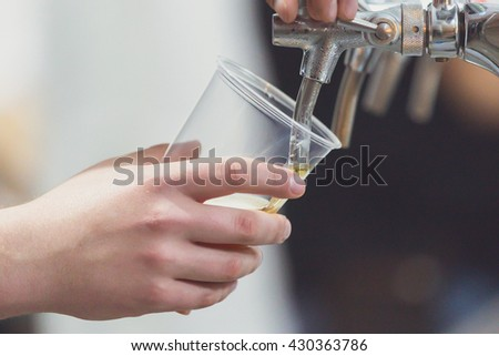 close-up of barman hand at beer tap pouring a draught  beer - stock photo