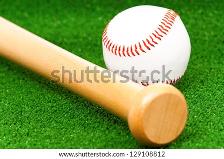 Close-up of baseball ball and bat on artificial green grass - stock photo