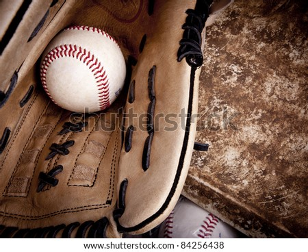 Close up of baseball glove with baseball in it laying on an aged home plate - stock photo
