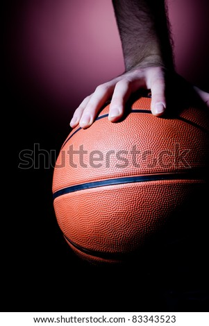 Close up of basketball player's hand on the ball - stock photo