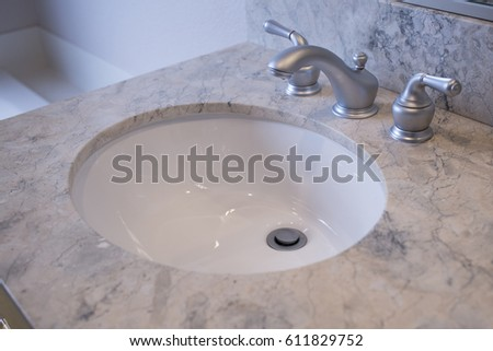 Close Up Of Bathroom Sink With Stainless Steel Faucet And Marble Counters
