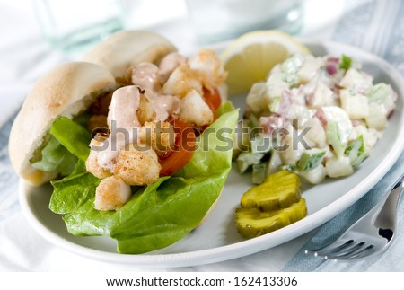 Close up of bay scallop sandwich with fresh red potato salad.