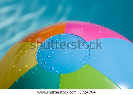 Close-up of beach ball with green, blue, pink,yellow and orange, water dropletts
