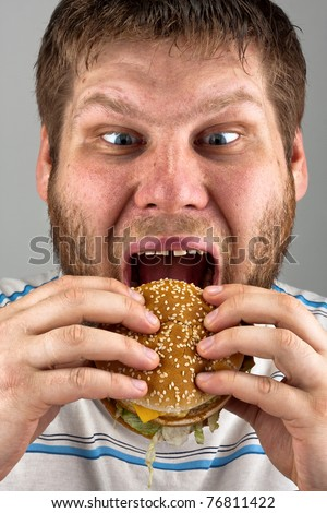 Close-up of bearded man eating juicy hamburger - stock photo