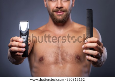 Close up of bearded naked man holding electric razor and comb. He is standing and showing tools to the camera. The man is smiling. Isolated on grey background