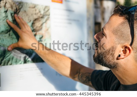Close-up of bearded tourist looking at mountain map in sunlight