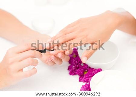 Close up of beautician applying nail varnish to female client nails at spa beauty salon - stock photo