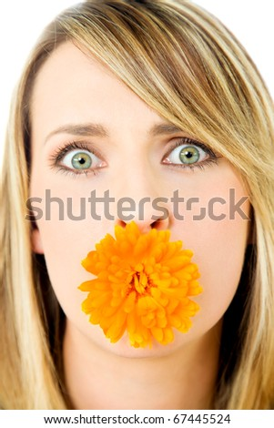 Close-up of beautiful blond female with marigold flower in mouth, staring at camera - stock photo