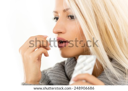 Close-up of beautiful blonde girl taking a pill. - stock photo