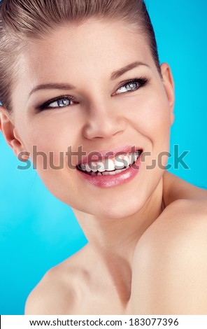 Close-up of beautiful blue eyed woman showing her healthy white teeth. Young attractive Caucasian female model with wide perfect smile over blue background.   - stock photo