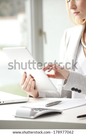 Close-up of beautiful businesswoman sitting at desk and typing on tablet in office.