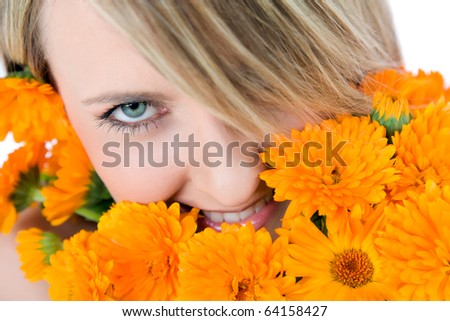 Close-up of beautiful female face holding marigolds, colourfull eye looking at camera - stock photo