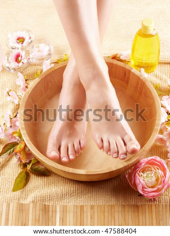 Close-up of beautiful female feet in wooden bowl filled with fluid cosmetics, flowers all around. Concept of natural spa treatment. - stock photo