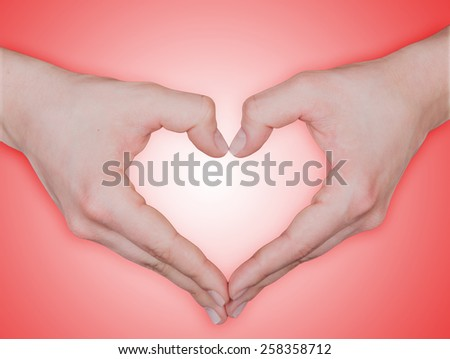 Close up of beautiful female hands form heart shape isolated on red background - stock photo