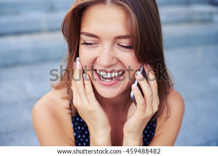 Close-up of  beautiful girl talking on the mobile phone with a broad smile on her face and looking down - stock photo