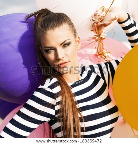 close-up of beautiful girl with smokey eye make up and long hair in black and white striped dress with bunch of multicolored balloons - stock photo