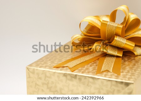 Close up of beautiful golden and elegant gift box with ribbon or bow for present for someone special - stock photo