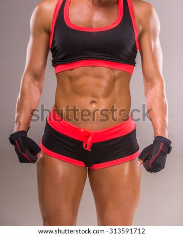 Close-up of beautiful muscular bodybuilder woman on gray background. - stock photo