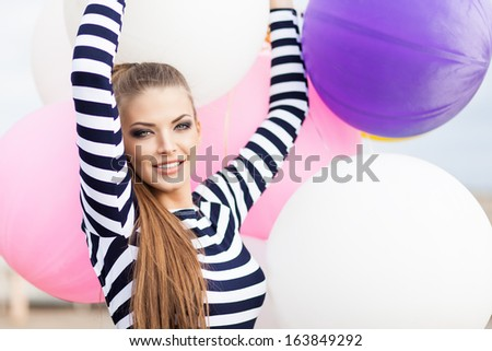 close-up of beautiful smiling girl with smokey eye make up, ponytail hair in black and white striped dress keeps her hands raised holding bunch of multicolored balloons - stock photo