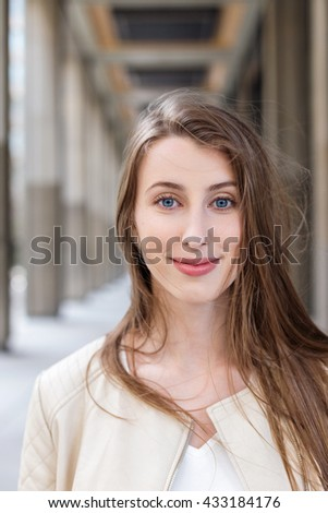 Close up of beautiful smiling teenage girl smiling at camera. University-looking building blurred perspective background  - stock photo