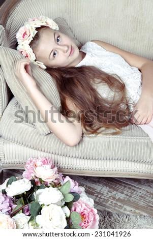 Close-up of Beautiful teenager girl lying on sofa near flowers  - stock photo