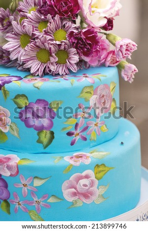 Close up of beautiful tree tiers hand painted floral cake in a garden party - stock photo