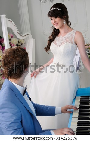 Close up of beautiful woman and man playing on piano. Wedding dress. Wedding accessories