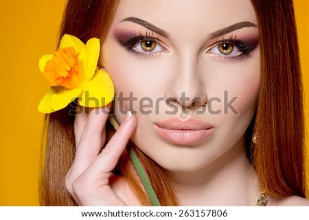 Close-up of beautiful woman face with colorful make-up and lips with  yellow flower - stock photo