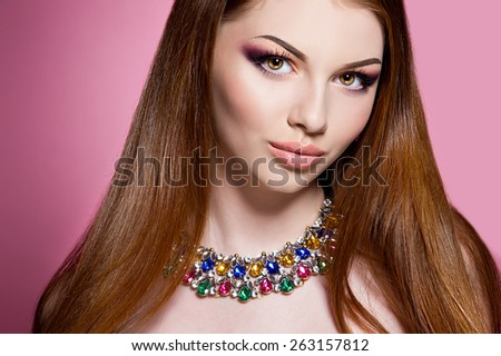 Close-up of beautiful woman face with colorful make-up and lips. Woman with colorful necklace  - stock photo