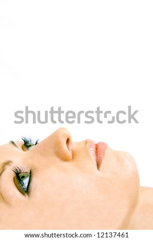 Close-up of beautiful woman face with green eyes. On white background