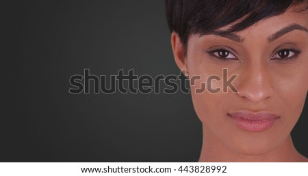 Close up of Beautiful woman with small smile on her face on grey background - stock photo