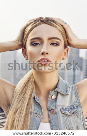 Close up of beautiful young  blonde woman staying on the rooftop. Wearing denim vest, necklace and white undershirt. Her hair is tied to ponytail. Professional make-up, hair style and styling. - stock photo