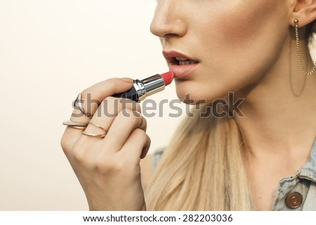 Close up of beautiful young  blonde woman which is painting her lips with red lipstick. Selective focus on lipstick with shallow depth of field. - stock photo