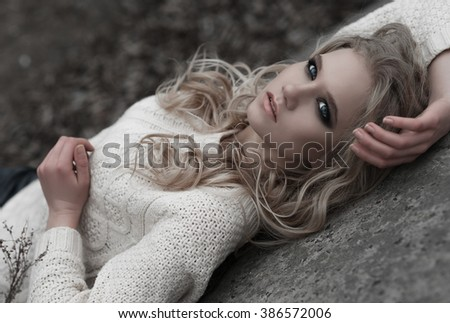 Close up of beautiful young  blonde woman with blue eyes in white pullover.  Winter, spring, outdoor portrait. Professional beauty make-up: dark smoky eyes and pale lips and hair style. - stock photo