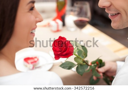 Close up of beautiful young loving couple celebrating Valentine day in cafe. The man is giving to a woman a rose. They are sitting at the table and smiling - stock photo