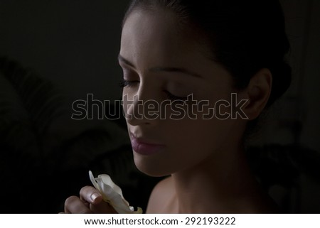 Close-up of beautiful young woman smelling flower - stock photo