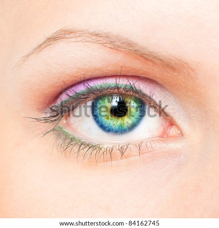 Close-up of beauty female eye with pink and green make-up