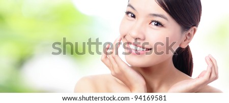 close up of Beauty woman Face and hand touch her face with green background, model is a beautiful asian girl - stock photo
